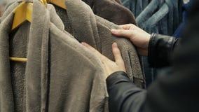 Close-upmening van mensen` s handen die een badjas in de opslag van bedlinnen en toebehoren kiezen stock videobeelden