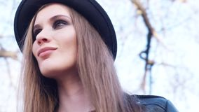 Close-upmening van mooie jonge vrouw in een donkere hoed en een zwart leerjasje die camera in de dag van de de lentezomer bekijke stock footage