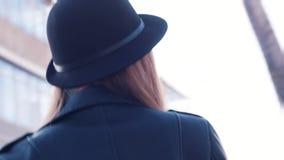 Close-upmening van mooie jonge vrouw in een donkere hoed en een zwart leerjasje die camera in de dag van de de lentezomer bekijke stock video