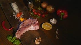 Close-upmening van ruw stuk van vlees en Spaanse peperspeper met vlam op zwart hakbord het lapje vleesbbq van het grillrundvlees  stock video