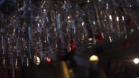 Close-upmening van schone en opgepoetste wijn en cocktailsglazen voor het hangen over de barteller Kader decoratie stock videobeelden