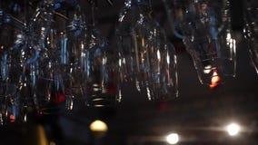Close-upmening van schone gewassen en opgepoetste glazen voor wijn en andere alcoholische dranken die over de barteller hangen stock footage