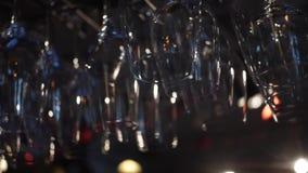 Close-upmening van schone gewassen en opgepoetste glazen voor wijn en andere alcoholische dranken die over de barteller hangen stock videobeelden