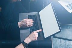 Close-upmening van twee jonge collega's die computer met behulp van bij modern huis Het lege witte laptop scherm Horizontaal visu Royalty-vrije Stock Afbeelding