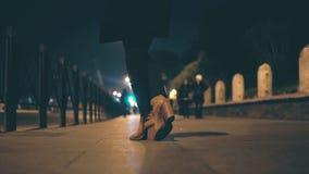 Close-upmening van vrouwelijke benen die schoenen op een hoge hiel dragen Vrouw die zich op de brug in avond en wachten bevinden Royalty-vrije Stock Foto