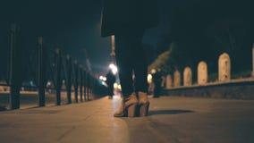 Close-upmening van vrouwelijke benen die schoenen op een hoge hiel dragen Vrouw die zich op de brug in avond en wachten bevinden Stock Foto