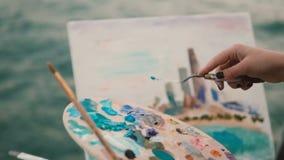 Close-upmening van vrouwelijke hand met borstel en palet die het beeld op de kust van het meer van Michigan, Chicago, Amerika sch stock footage