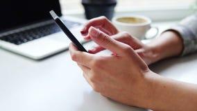 Close-upmening van vrouwelijke handen die app op smartphone gebruiken terwijl het zitten in koffie met een kop van koffie en lapt stock videobeelden