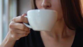 Close-upmening van vrouwelijke handen die een witte kop met hete thee van de houten lijst nemen Dan camerabewegingen omhoog met e stock videobeelden