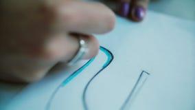 Close-upmening van vrouwens hand het kleuren lay-out van schoenen met blauw potlood Jonge ontwerper die nieuwe inzameling ontwikk stock video