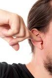 Close-upmens die een vinger in zijn oor met oor het aftappen, isola houden stock fotografie