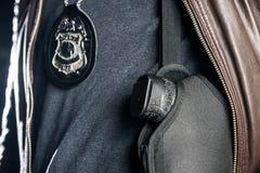 Close-upmidsection van politieman met kenteken en kanon in holst royalty-vrije stock afbeelding