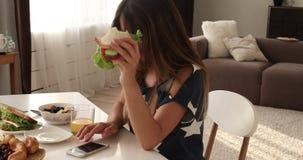 Close-upmond van aanbiddelijke hongerige vrouw die smakelijke sandwich eten die van voedsel genieten stock video