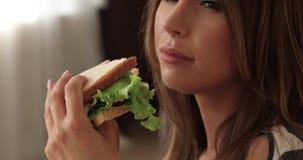 Close-upmond van aanbiddelijke hongerige vrouw die smakelijke sandwich eten die van voedsel genieten stock videobeelden