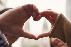 close upp Älska par som tillsammans sätter händer Beskriva gesthjärta royaltyfria foton