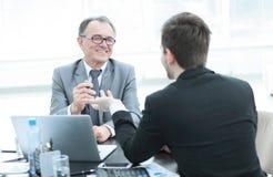 close upp affärsfolk som talar på ett skrivbord arkivbild
