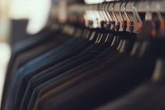 close upp Affärsmäns dräkter hänger på hängare i boutique av affärskläder Stort val av dräkten royaltyfri fotografi