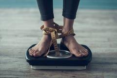 close upp Anseende för ung kvinna på weigheren på golv royaltyfri bild