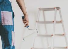 close upp Arbetare som går att måla med målarfärgrullen royaltyfria bilder