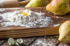 close upp Brutet vaktelägg i en kulle av vitt mjöl som omges av mogna stora päron lantlig livstid fortfarande brunt trä för bakgr royaltyfri bild