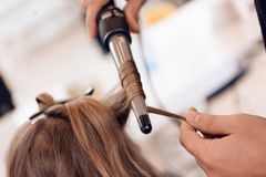 close upp Den bruna hårkvinnan gör krullande hår i skönhetsalong Frisören gör hår att vinka för kvinna royaltyfri fotografi