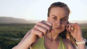 close upp Den ilskna flickan för sparkboxning utför utbildning på överkanten av berget på solnedgång eller soluppgång på sommar 1 lager videofilmer