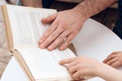 close upp Den uppsökte fadern med den lyckliga sonen läser boken som sitter på soffan arkivfoton