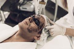 close upp Doktor Doing Cosmetic Procedure för man arkivbild