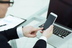 close upp en affärsman använder en smartphone i arbetsplatsen arkivfoto