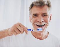 close upp Hög man som borstar tänder i badrum arkivbilder