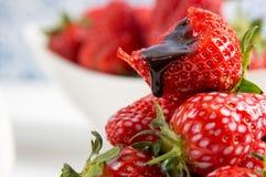 close upp lantlig livstid fortfarande Fl?den f?r choklads?s ner p? en biten ljus r?d jordgubbe En bunke av b?r p? en bakgrund arkivbild