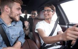 close upp lyckliga vänner som talar i bilen arkivfoto