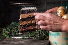 close upp Någon händer tjänar som ett klippt stycke av det nya årets chokladkakan på ett träbräde Stranda av hår vänder mot in royaltyfri bild