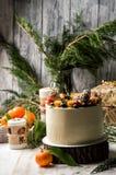 close upp Nytt års kaka, dekorerade blåbär, jordgubbar, kumquat Närliggande är orange tangerin som bränner festliga stearinljus arkivfoton