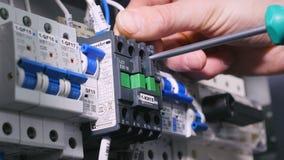 close upp Oigenkännlig yrkesmässig elektriker som monterar den elektriska skölden lager videofilmer