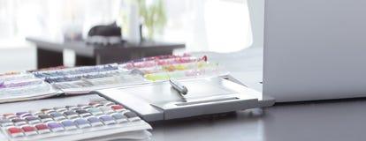 close upp penn-, anteckningsbok- och tygprövkopior på tabellen på den märkes- kläderna arkivfoto