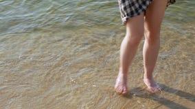 close upp Sexiga kvinnliga ben går på havet Kallt havsvatten lager videofilmer