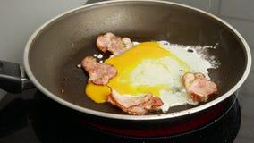 close upp Två ägg bryter in i en varm stekpanna med stekt bacon Frukost och k?kbegrepp stock video
