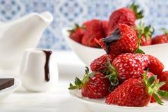 close upp Vitt tefat med en glidbana av saftiga jordgubbar Ett bitit bär ligger överst, med en droppe av choklad som flödar från  arkivbilder