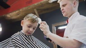 close upp Yrkesmässig barberare som gör en ny frisyr med hjälpen av kanten och den elektriska rakapparaten Pys och stylist eller arkivfilmer