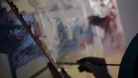 Close-uppalet met verf en canvas de kunstenaar trekt een beeld schildert een beeld Licht van het venster stock video