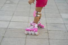 Close-uppanning kinderenrol het schaatsen Het leren openlucht te schaatsen Stock Foto