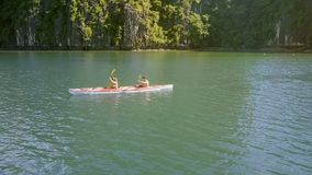 Close Upper View Blond Girl Brunette Guy Row Kayak in Ocean. Close upper view blond girl with ponytail and brunette guy row kayak on tranquil turquoise bay water stock footage