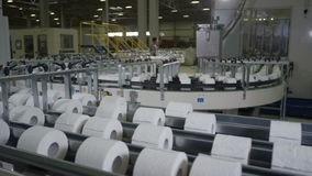 Close Upper View of Long Toilet Paper Conveyor. Close upper panoramic view of long conveyor with toilet paper moving slowly in large light factory workshop stock footage