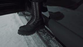 Close-uppersoon in zwarte rotsschoenen die van auto weggaan stock video