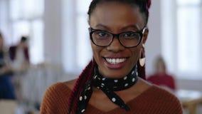 Close-upportret dat van jonge slimme Afrikaanse bedrijfsvrouw in oogglazen met ernstige blik, toen gelukkig op kantoor glimlacht stock video