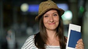 Close-upportret die van Aantrekkelijk het Glimlachen Brunette in de Zomerhoed op Haar Vliegtuig bij de Luchthaven met Kaartje wac stock video