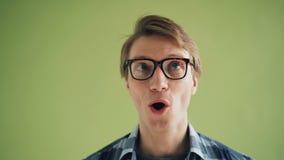 Close-upportret die van dwaze mannelijke studenten roterende ogen grappige gezichten maken stock videobeelden