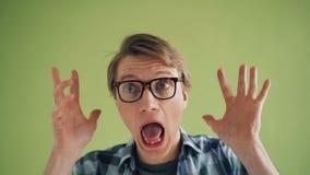 Close-upportret die van gekke kerel grappige gezichten maken bekijkend camera en het lachen stock videobeelden