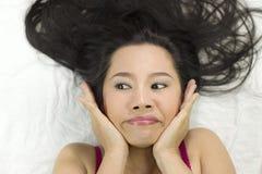 Close-upportret die van gelukkige Aziatische vrouwen op grond met zwart lang haar liggen acterenglimlach, pret stock afbeeldingen